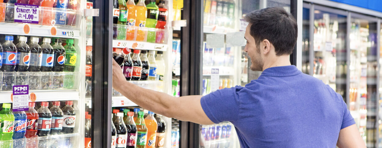 Man choosing beverage from cold case