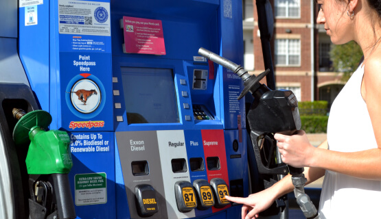 Woman using fuel dispenser