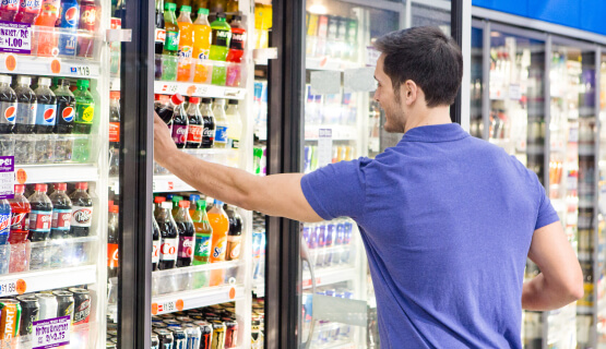 Man choosing drink from cold case