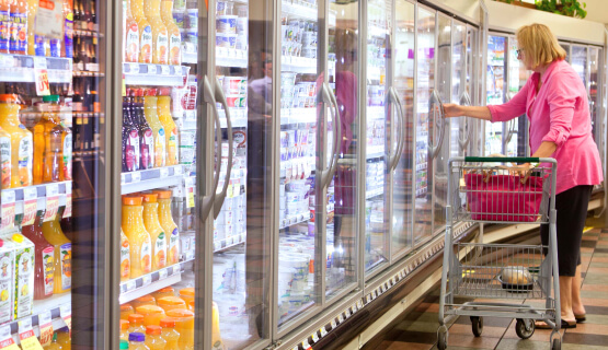Woman browsing cooler section of grocery